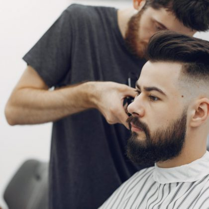 Man with a beard. Hairdresser with a client. Brunette in a barbershop
